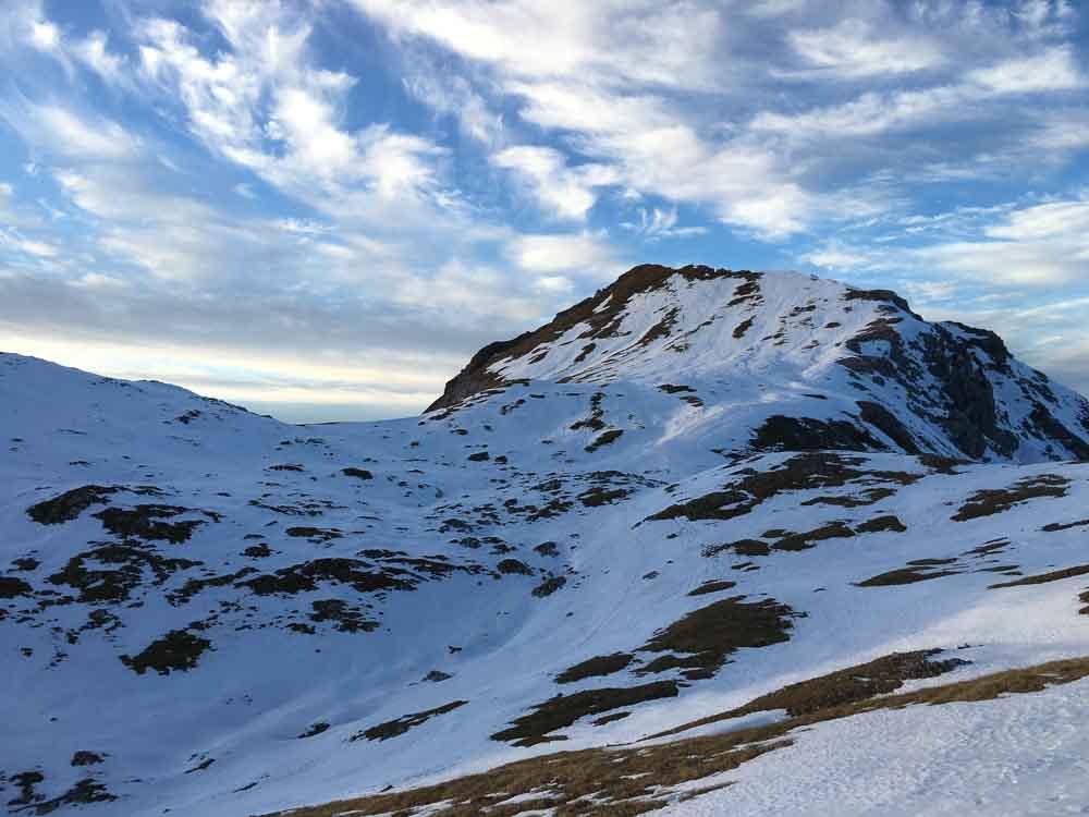 Sanfte Bergrücken in Abenstimmung, der Weg geht nach links unten weg über den Hang.