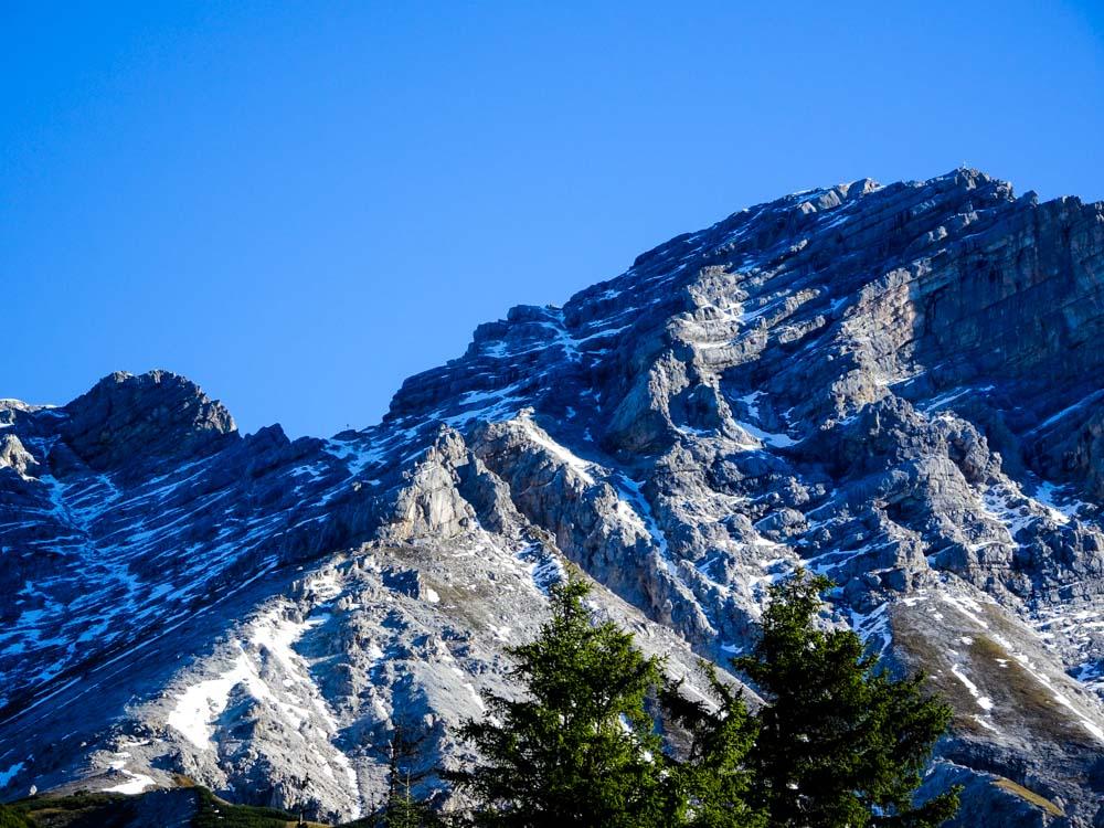 Aufstieg entlang des Grats, bei den ersten Felsen quert der Weg in die schattige Westflanke