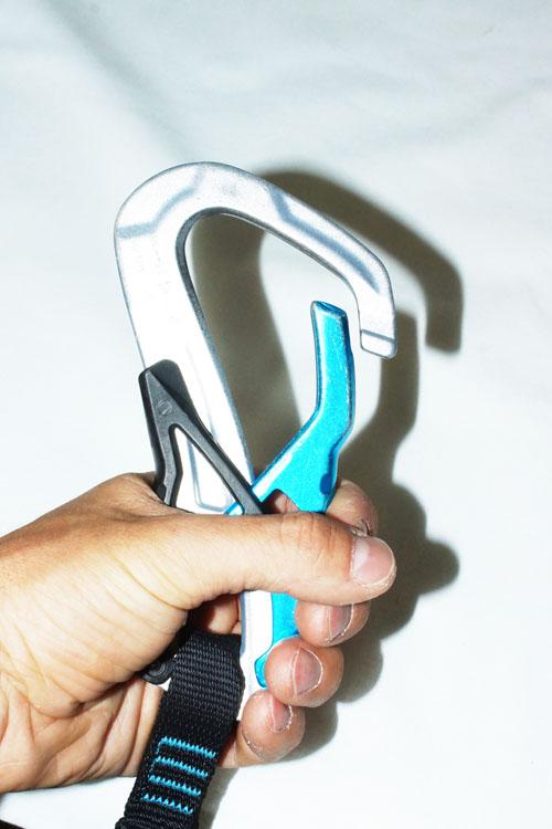 Der Mechanismus öffent den Schnapper oben durch das Drücken der schwarzen Gegenvorrichtung hinten mittels Handballen.