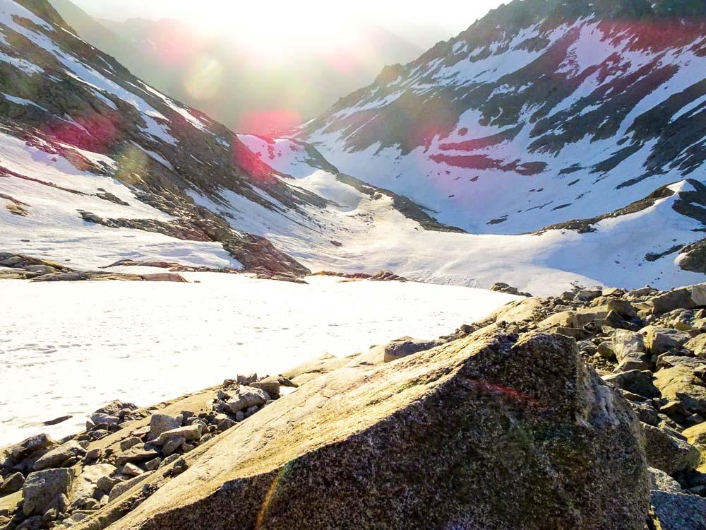 Über Schneefelder und Felsen geht es zur Rinne.